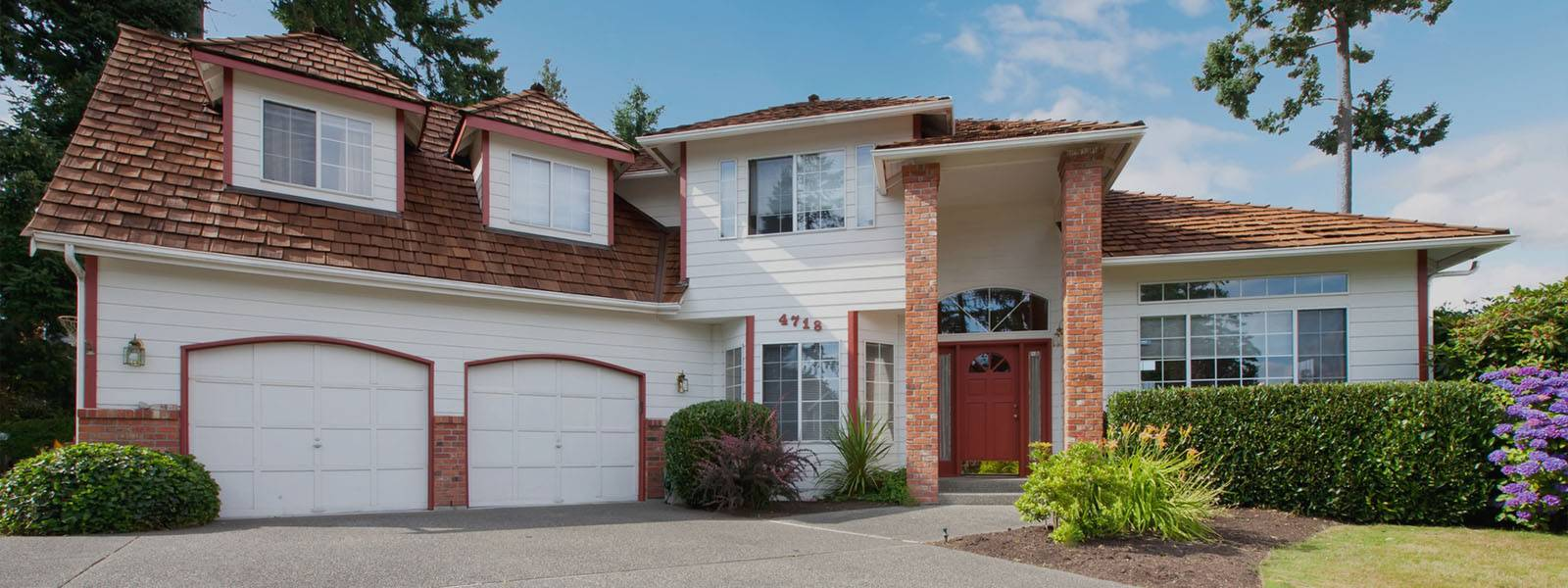large house with double garage doors in white